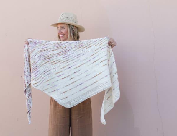 Woman holding an asymmetrical Tunisian crochet shawl made with Lion Brand Hand-Dyed Heaven yarn. (Lady Marmalad)