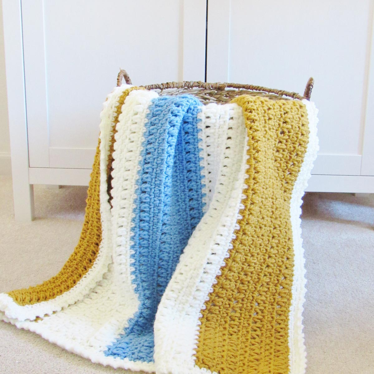 Easy crochet blanket for beginners laying on the side of a brown whicker basket. The blanket has wide stripes of white, gold and light blue.