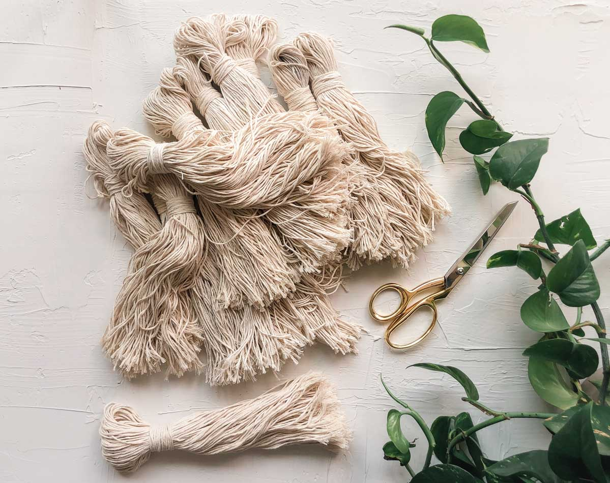 A pile of tassels made from cotton twine that are being used for a DIY tassel wall hanging.
