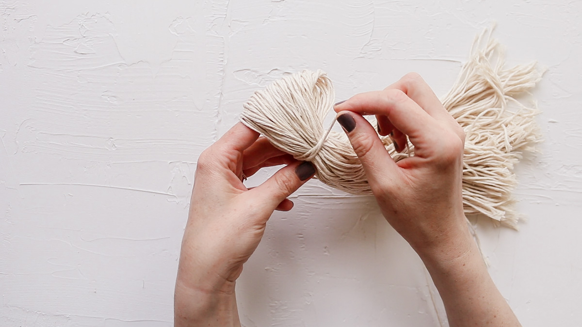 A close up of a woman's hands making a DIY yarn wall hanging with dollar store twine.