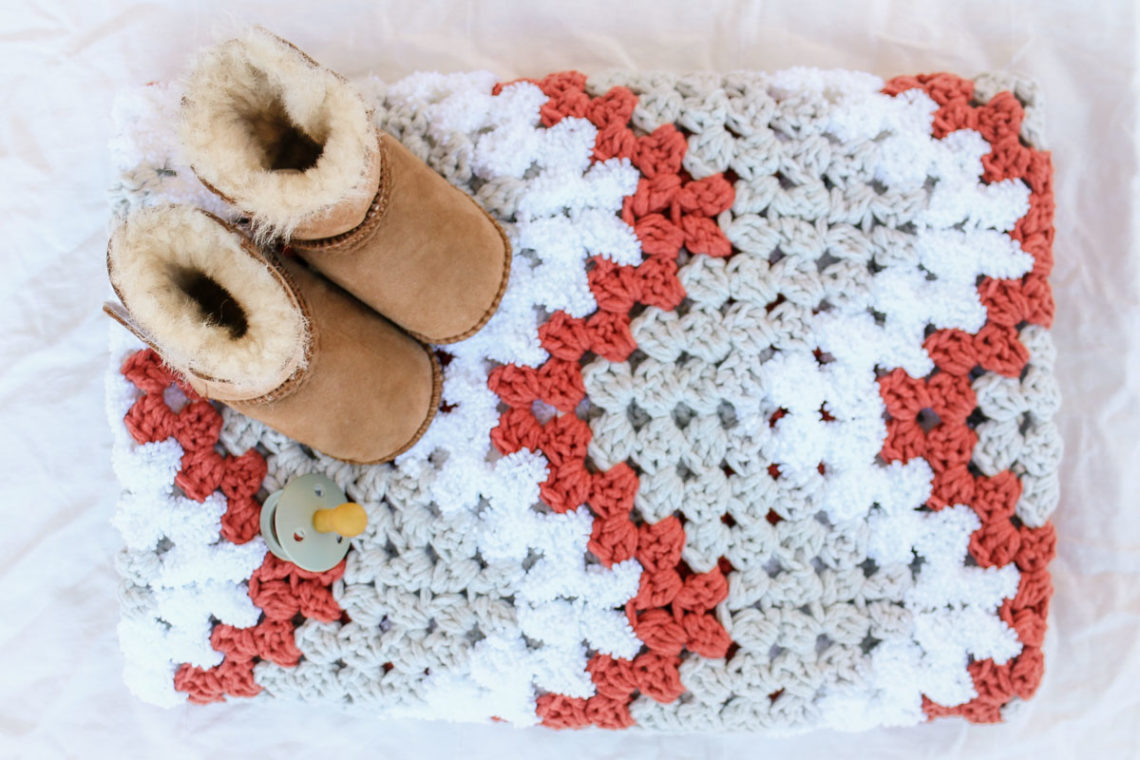 Adorable baby sitting on a easy crochet baby blanket made from a free crochet pattern using Lion Brand yarn.
