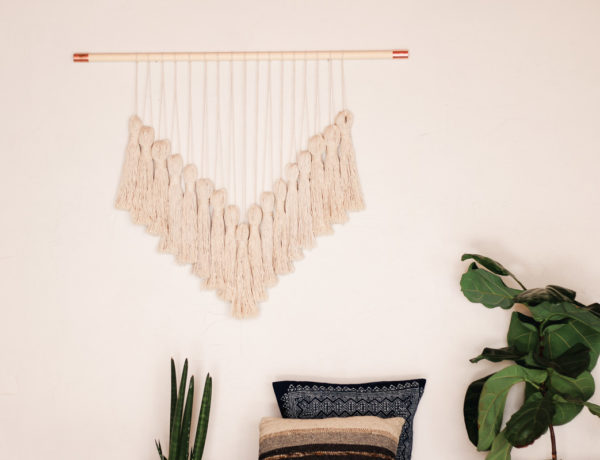 A beautiful DIY yarn wall hanging in a boho living room. The wall hanging uses copper pipe fittings to add a bit of glam.