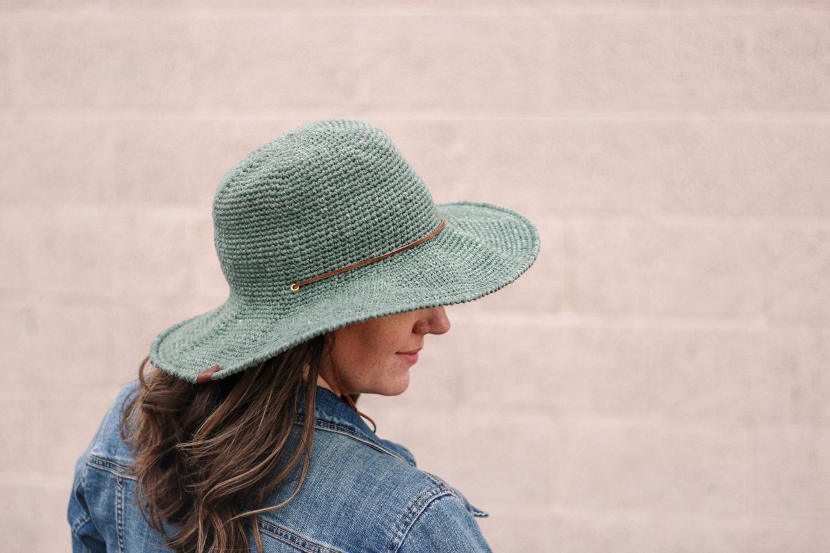 Brown haired woman wearing a crocheted sun hat with a stiff brim.