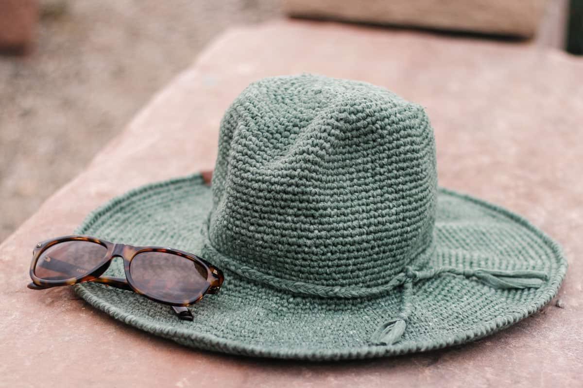 A crochet fedora sun hat sitting on a rock.