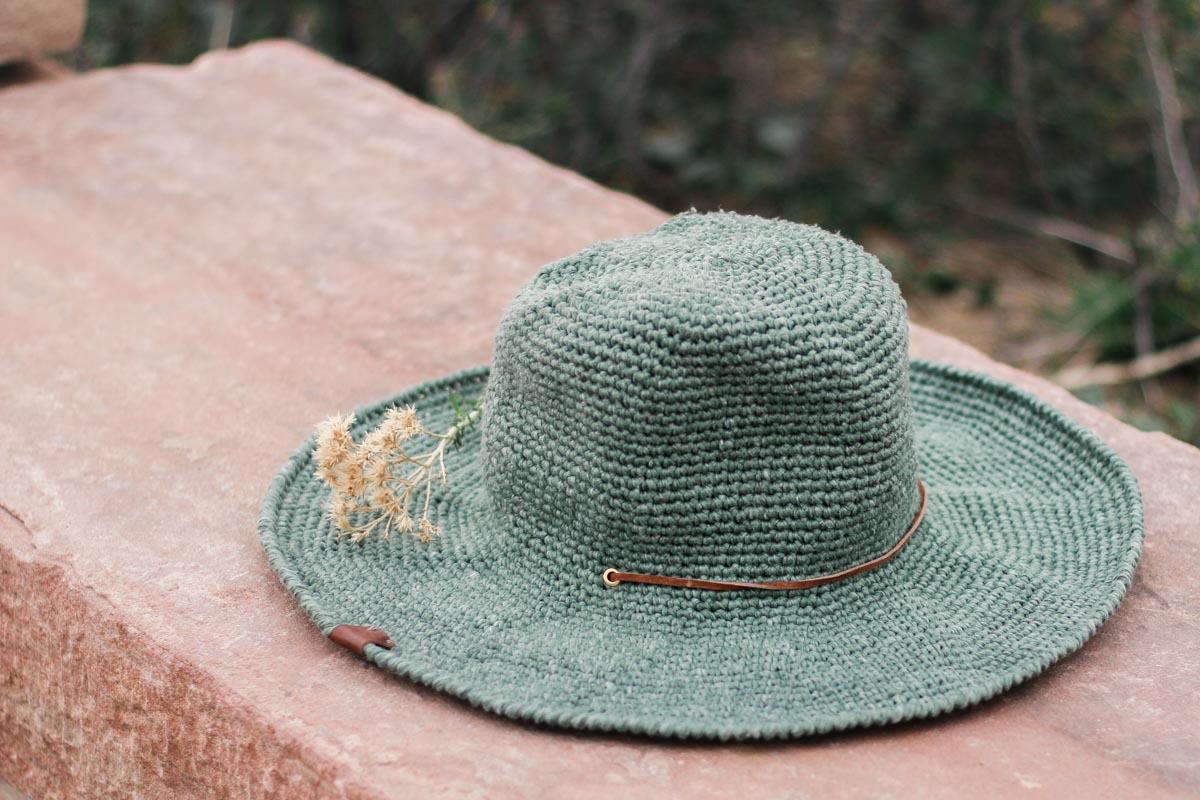 "A crochet fedora sun hat made with Lion Brand Rewind Yarn in the color ""Olive You"" with grommets and a chin strap."