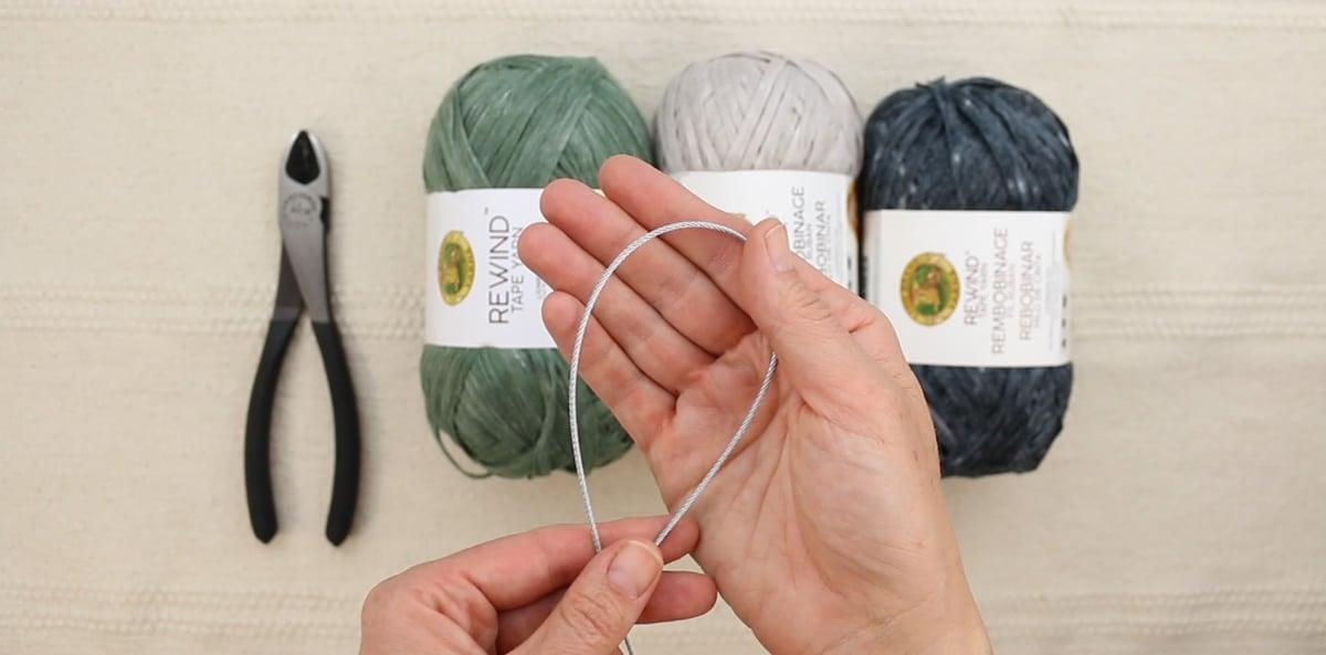 A hand holding galvanized wire rope above three skeins of Lion Brand Rewind yarn.