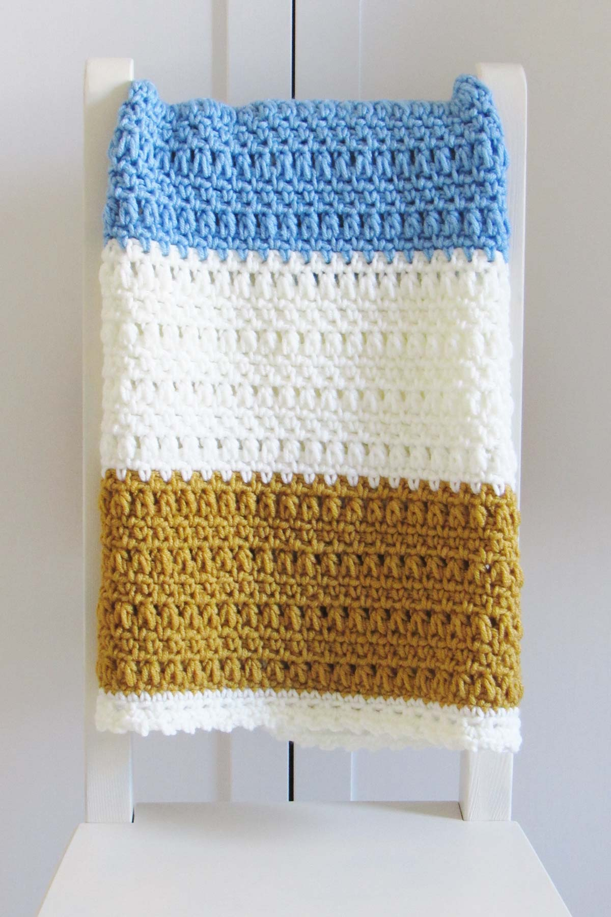 Easy crochet blanket for beginners folded in a rectangle and placed on the back of a white chair. The blanket has wide gold, white and light blue stripes.
