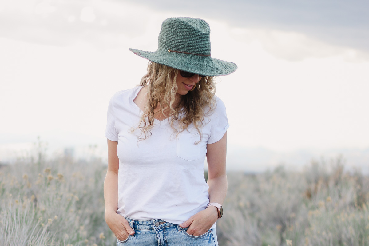 Woman standing in a field wearing a fedora crochet sun hat made with raffia-like yarn.