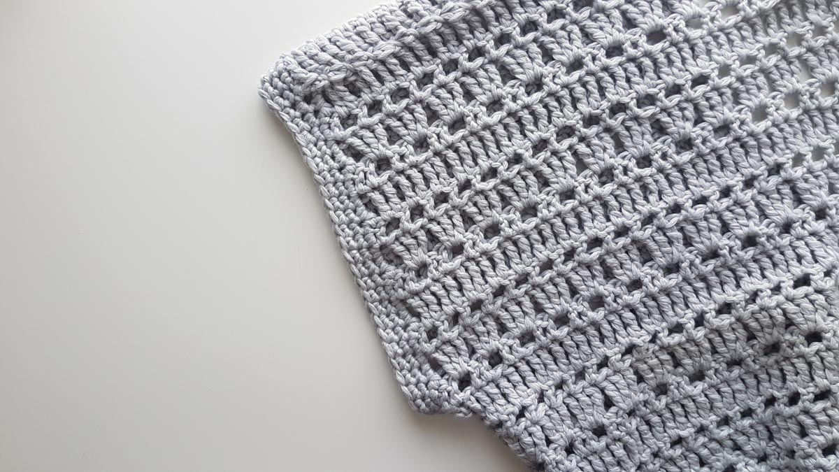 Photo of the sleeve of a short sleeve crochet cardigan. The photo is focusing on the crochet stitch used.