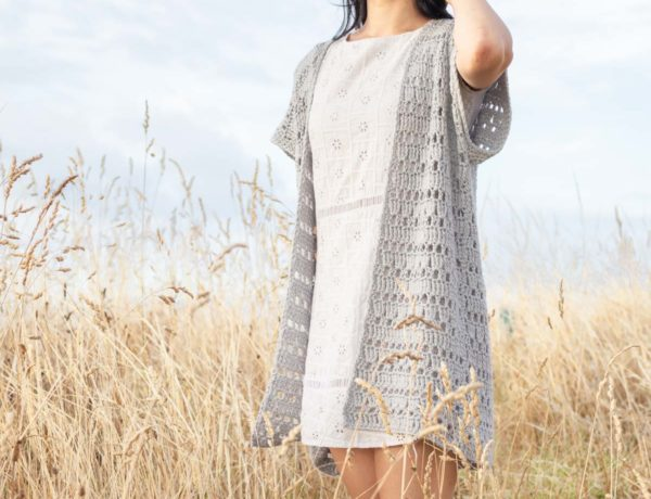 Women standing in field wearing a white dress and a lacy gray crochet cardigan. Her hand is touch the back of her sun hat.