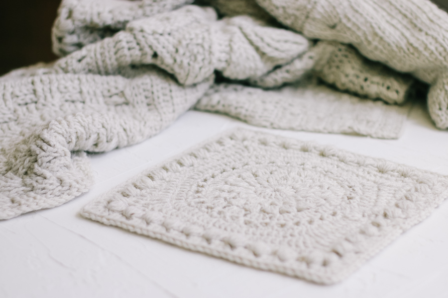 A moody shot of a crochet afghan square with the work in progress crochet sampler blanket in the background.