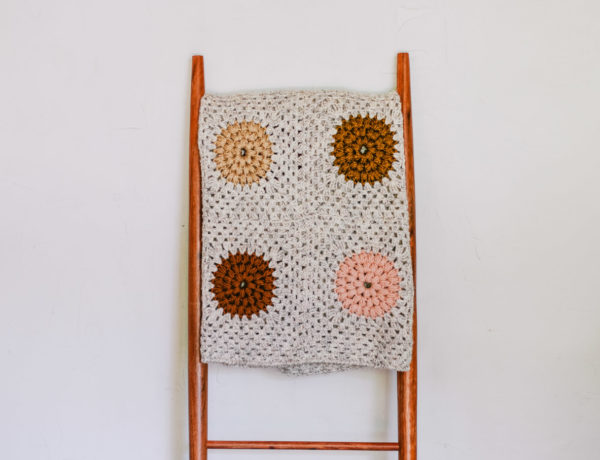 Crochet puff stitch granny square blanket hanging on a mid century blanket ladder.
