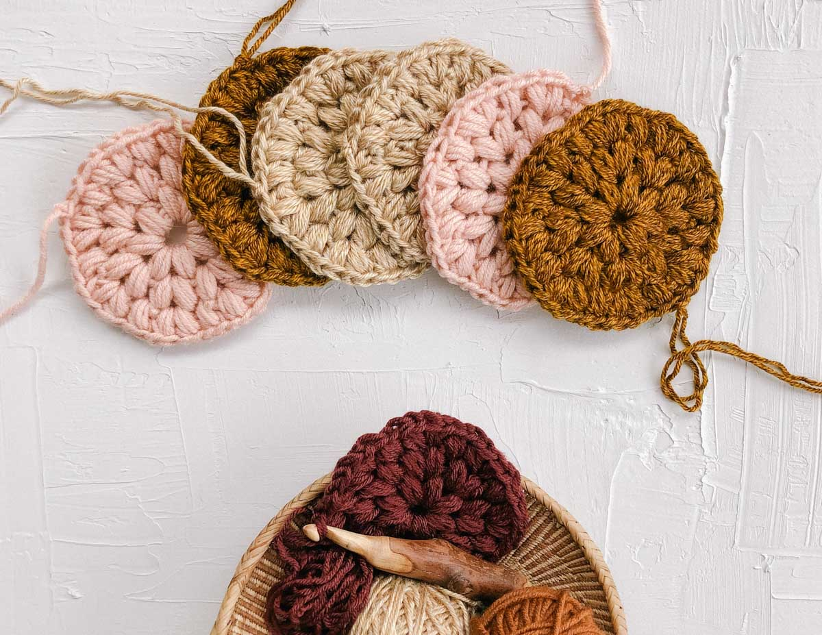 Six crochet puff stitch circles made with warm colored yarn. They look almost like crochet puff stitch flowers.