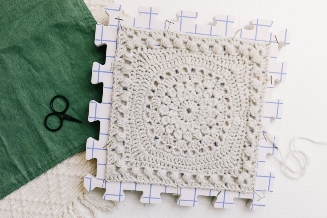 A crochet square made with bobble and puff stitches pinned to a foam blocking board.