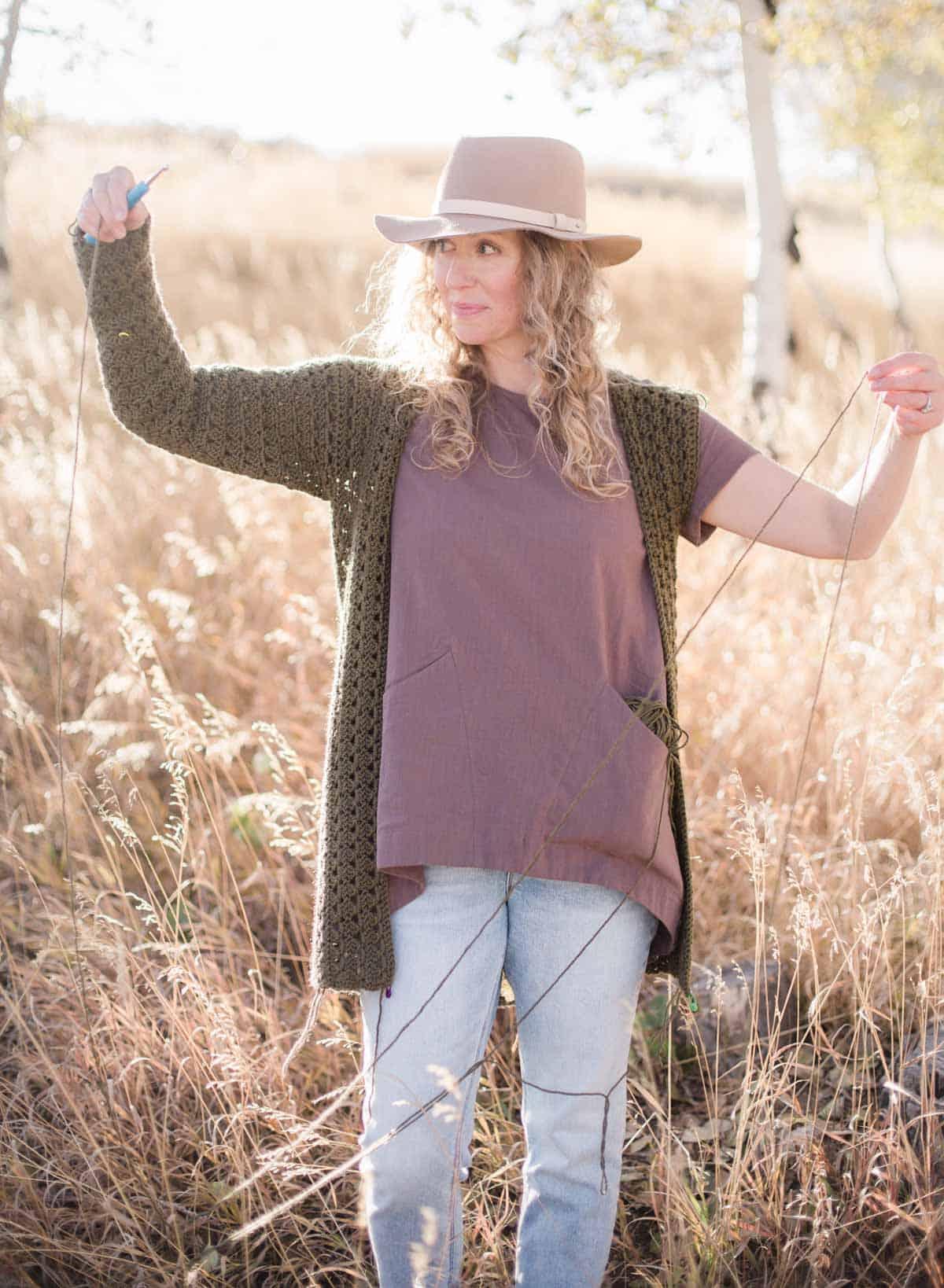 Jess Coppom, a crochet blogger, wearing a half-finished crochet sweater.