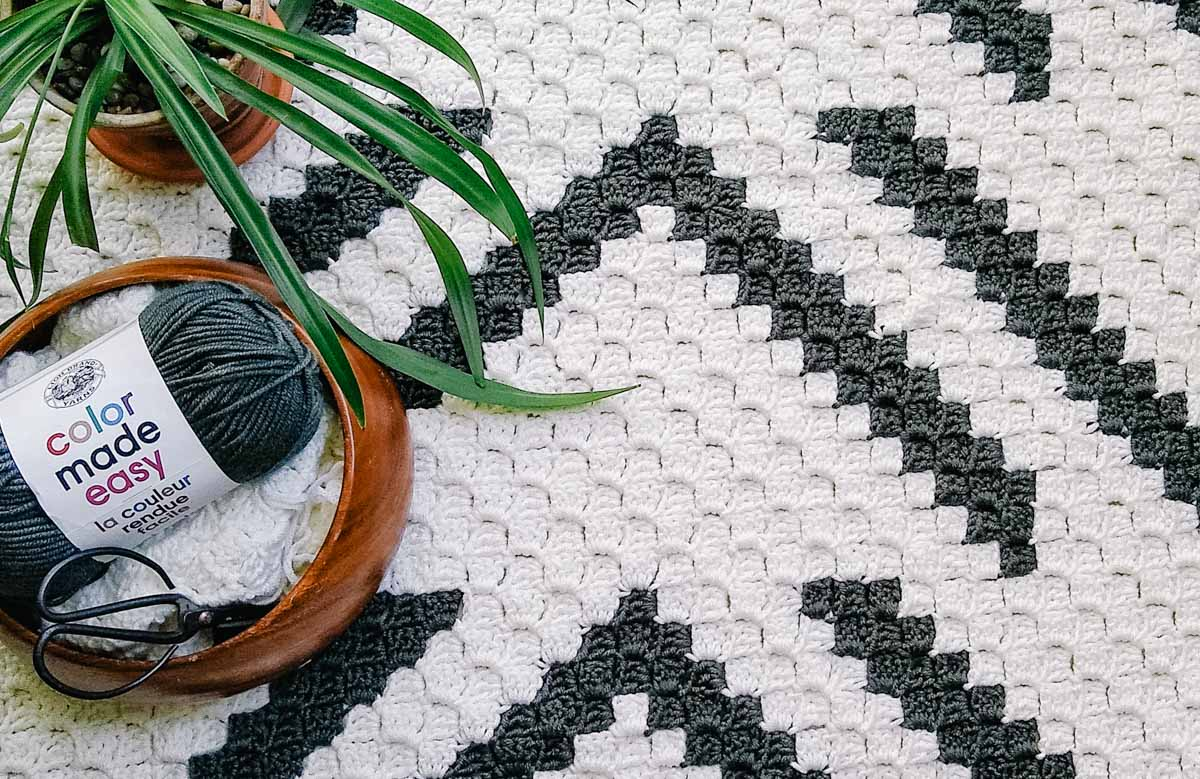 A modern c2c crochet blanket with Lion Brand Color Made Easy yarn on top of it.