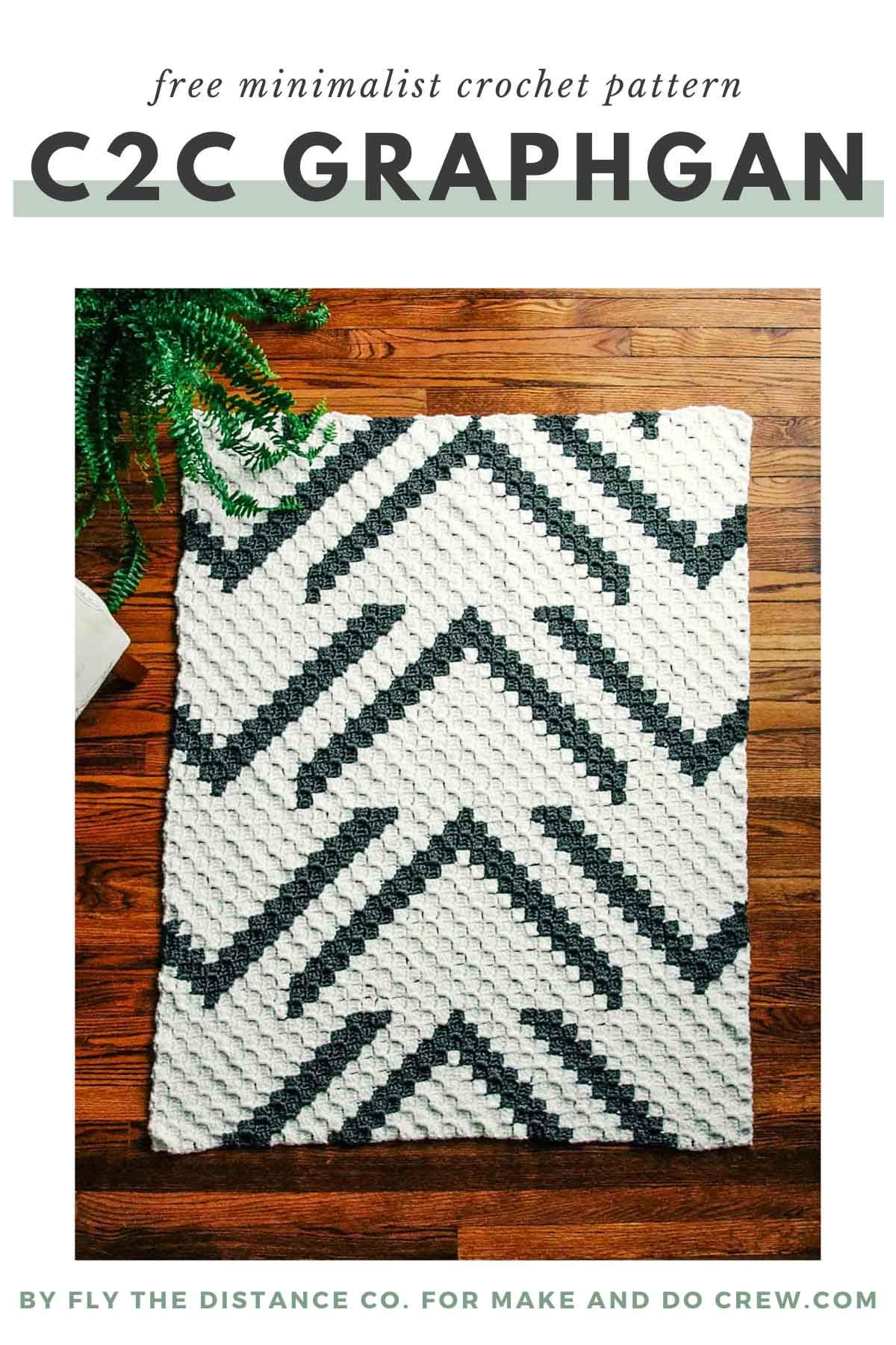 A modern c2c crochet blanket laying on a wood floor. The blanket has stylish pattern of arrows.