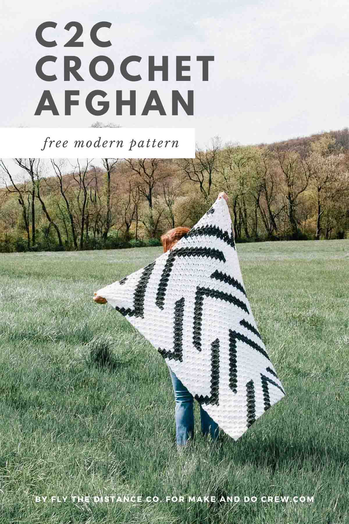 A woman in a field holding up a corner to corner crochet blanket with arrows on it.