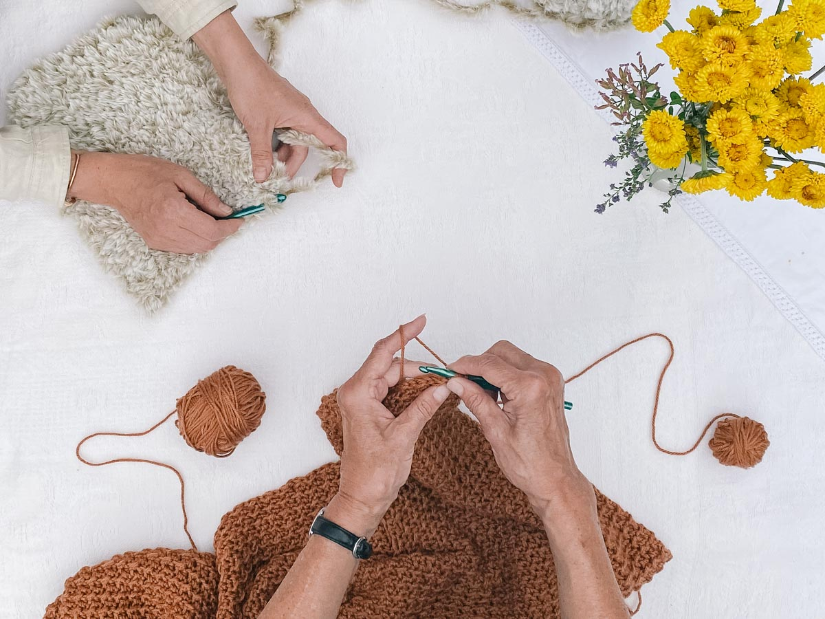 An older woman's hands and a younger woman's hands, both crocheting side by side.