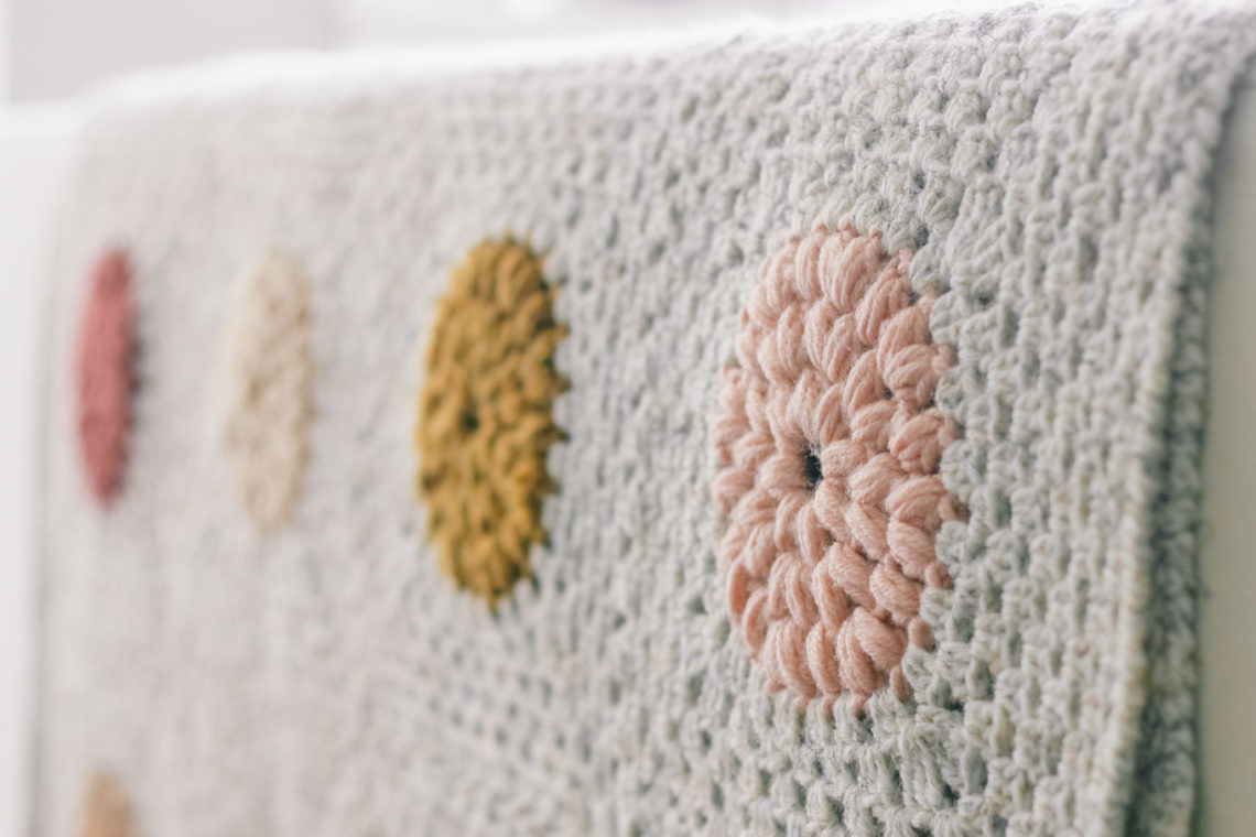 Close up of crochet blanket edging made with the reverse single crochet (crab stitch). The blanket features crochet puff stitch circles made with scrap yarn.