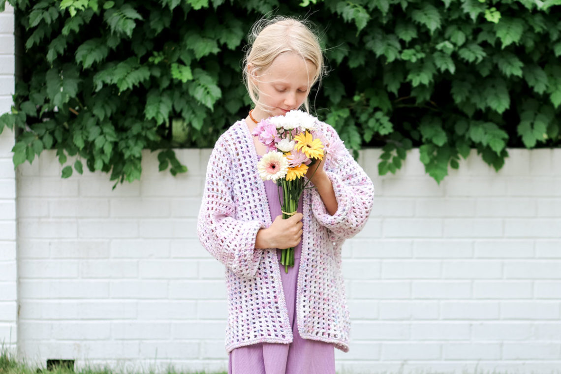 A young child wearing a casual crochet cardigan made with hand dyed yarn.