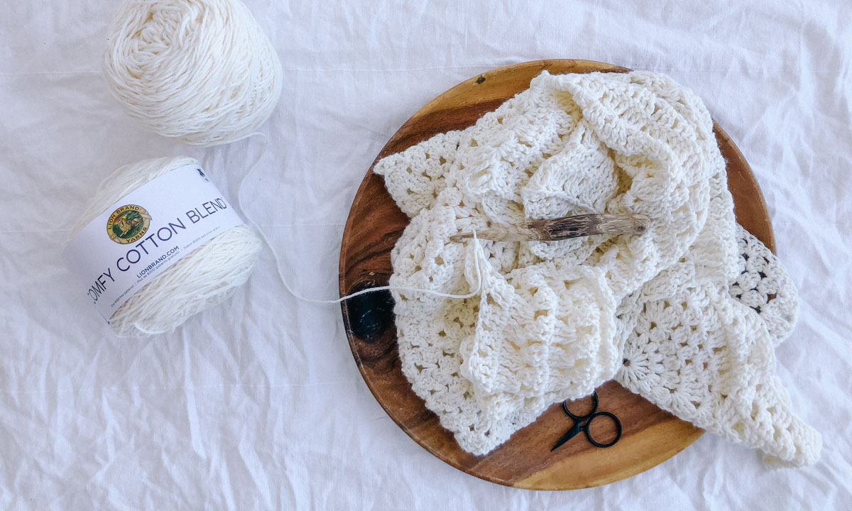 A boho crochet vest in progress being crocheted with Lion Brand Comfy Cotton Blend in the color Whipped Cream.