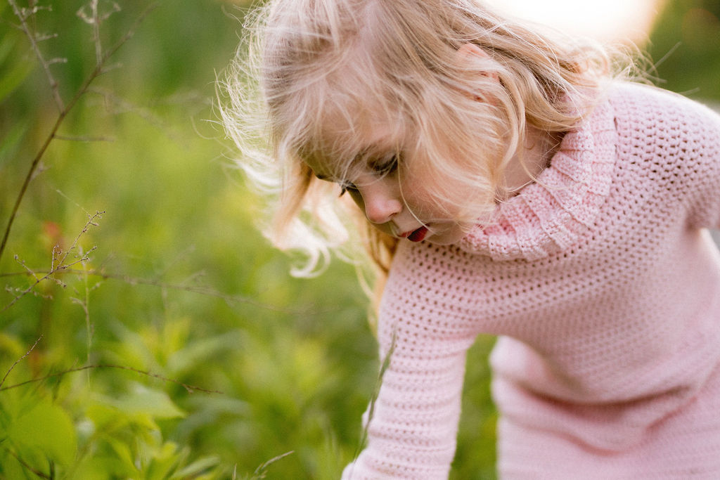 Girl in a pink crochet sweater dress bending over to pick wild flowers in a green field.