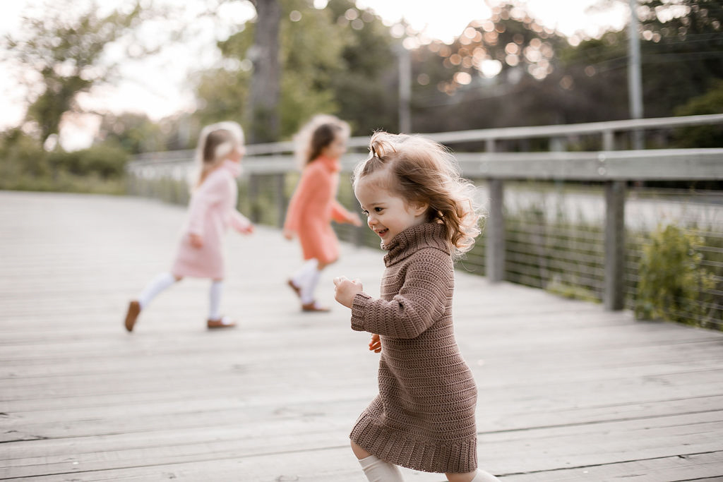 Three girls running around and playing on a wooden bridge. They are wearing crochet sweater dresses.