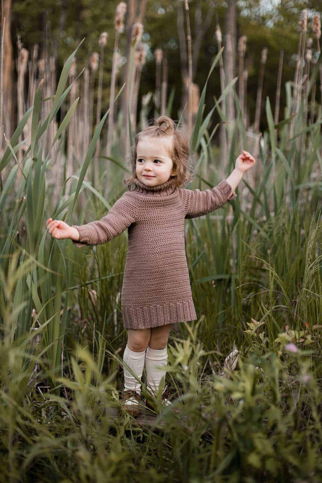 Toddler girl standing in field of tall green grass, wearing a brown crochet sweater dress.