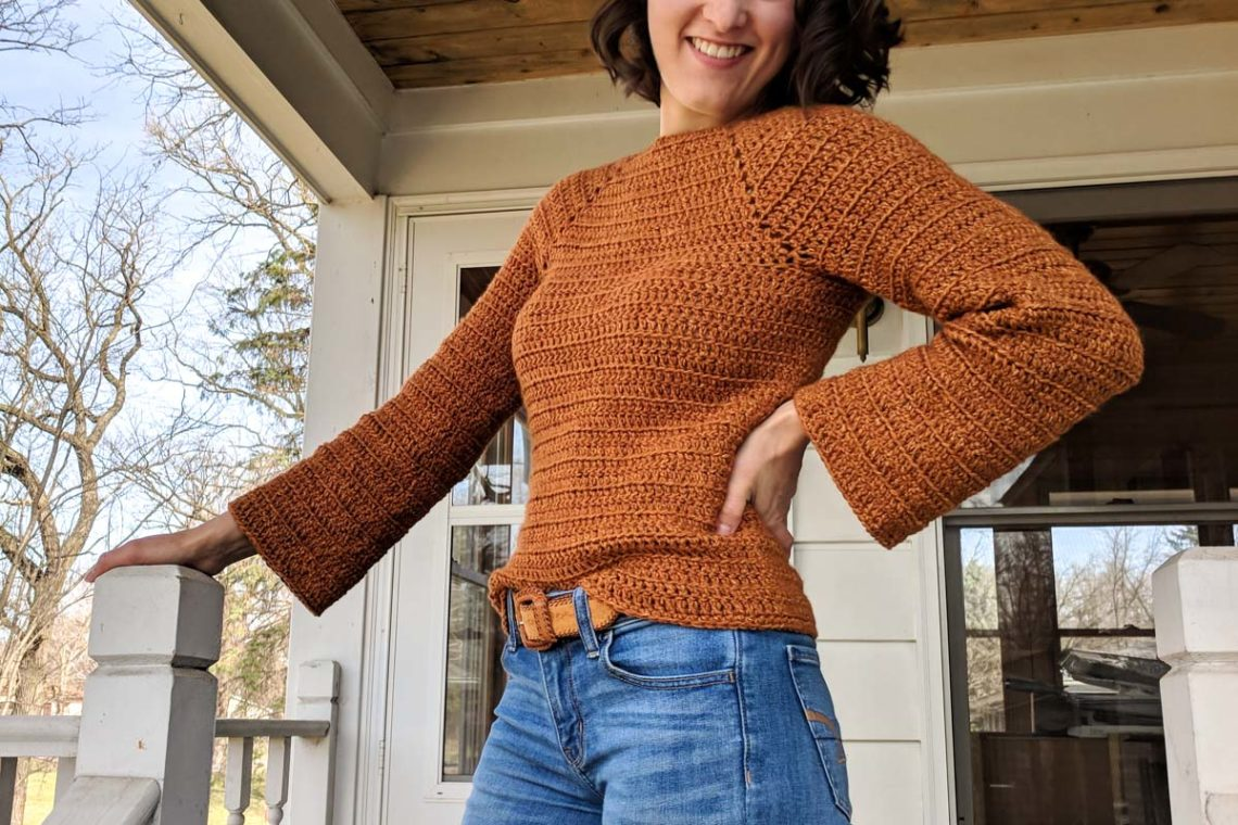 Girl standing outside on front porch of house. She has her hand on her hip and is wearing jeans with a burnt orange crochet sweater with bell sleeves.