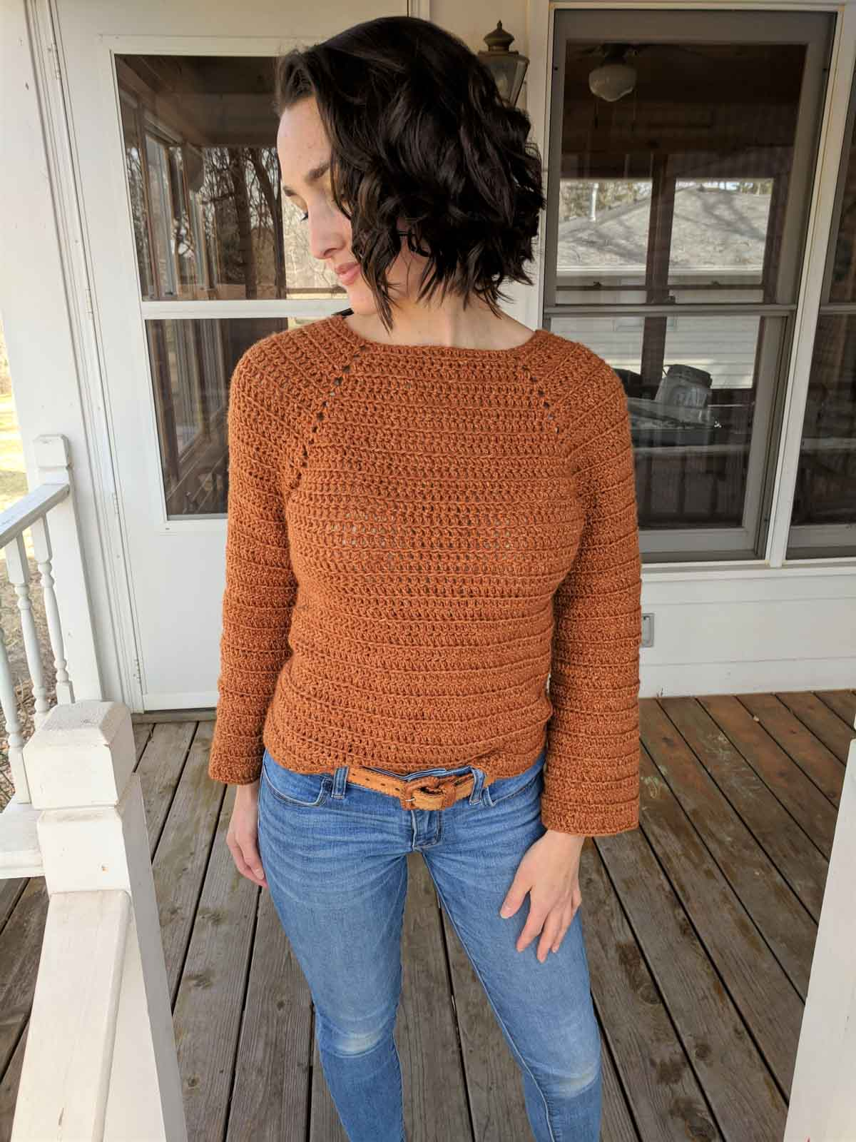 Girl standing outside on front porch of house, wearing blue jeans and a burnt orange crochet sweater.