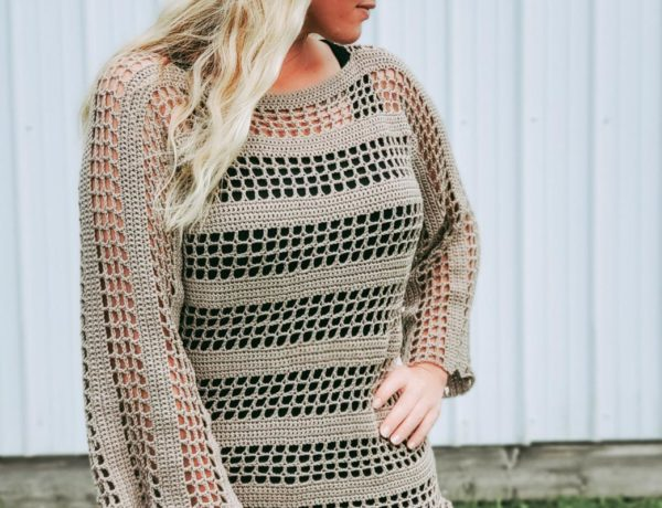 Woman standing outside in front of a white wall, wearing a lightweight crochet sweater with a black tank top underneath.