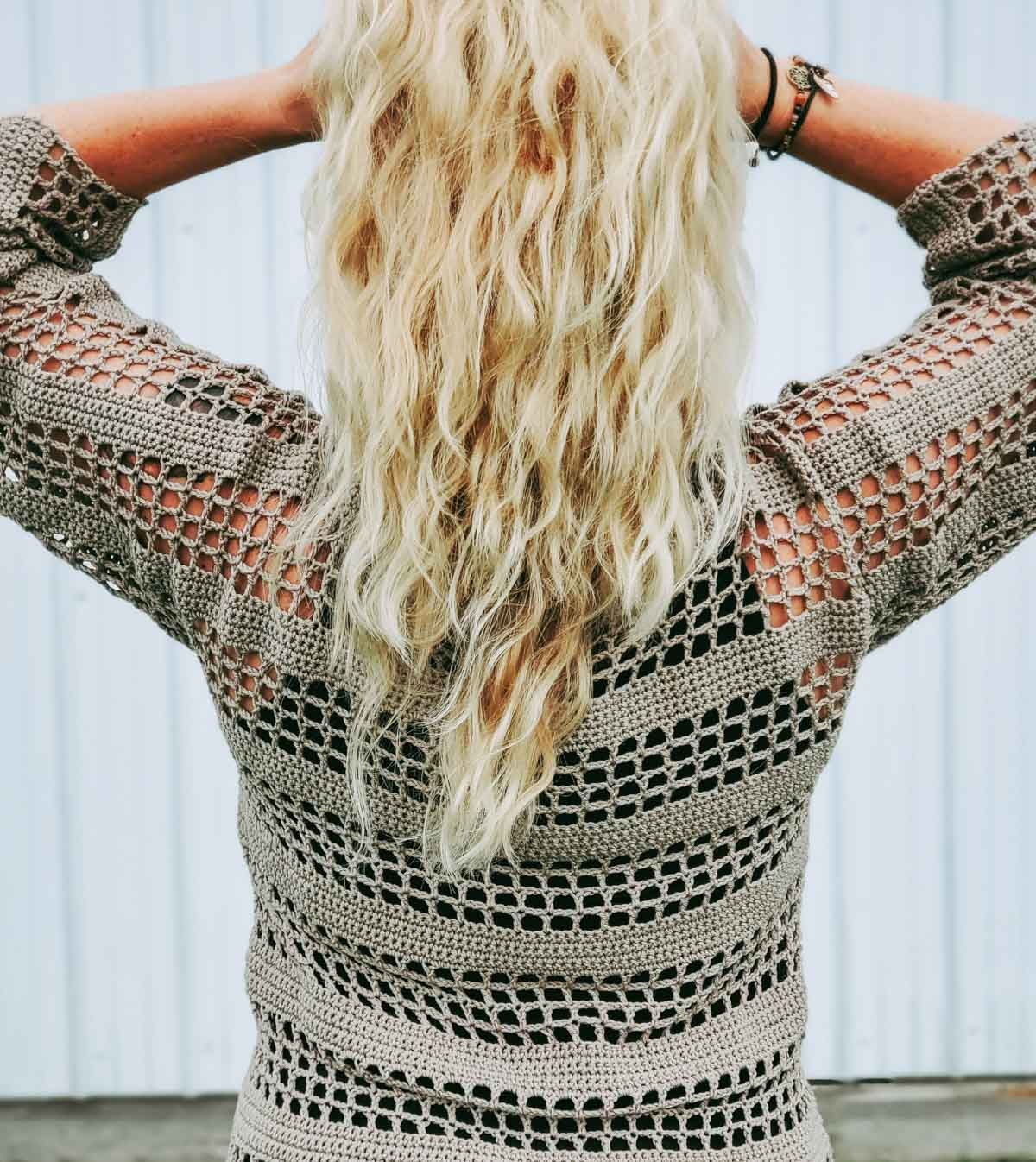 Woman standing outside in front of a white wall. She is pulling her hair up with her hands to show the back of her lightweight crochet top.