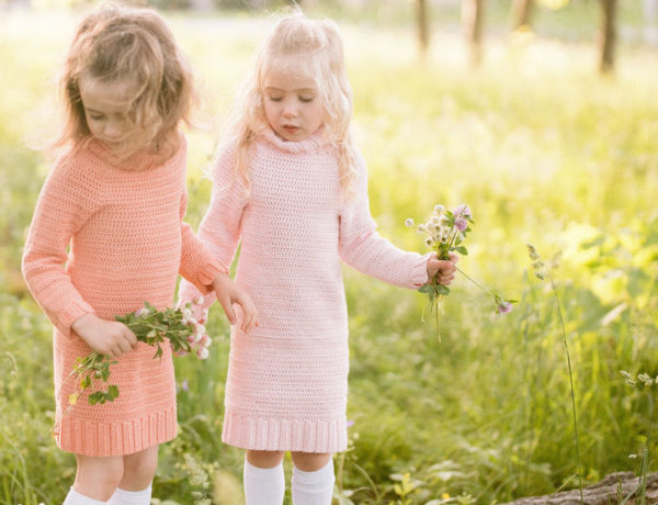 Two girls standing in a field of green grass, wearing crochet sweater dresses and each holding a bouquet of wild flowers.