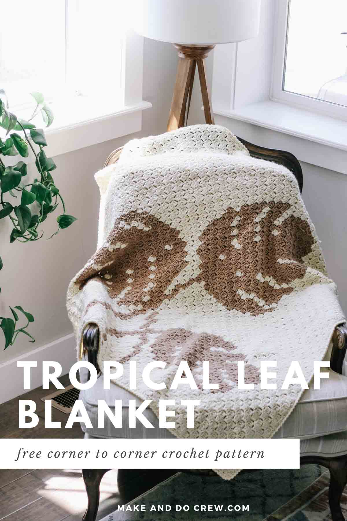 A monstera leaf corner to corner crochet blanket draped over a modern chair in a sunroom.