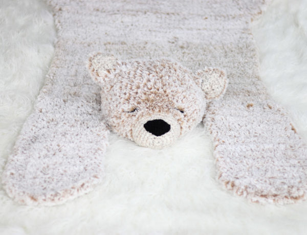 A crocheted faux fur bear blanket rug laying on a white floor.
