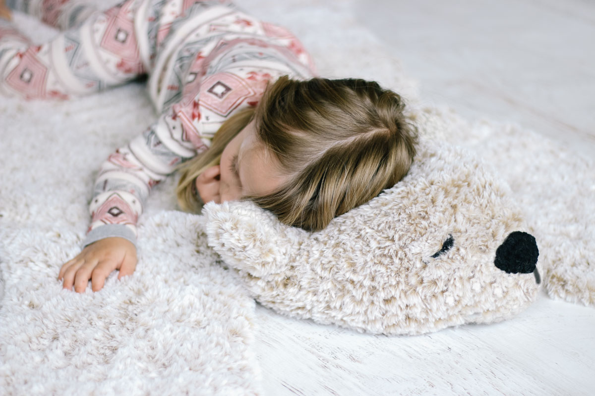 Young girl sleeping on a faux fur bear rug crocheted from a free pattern.
