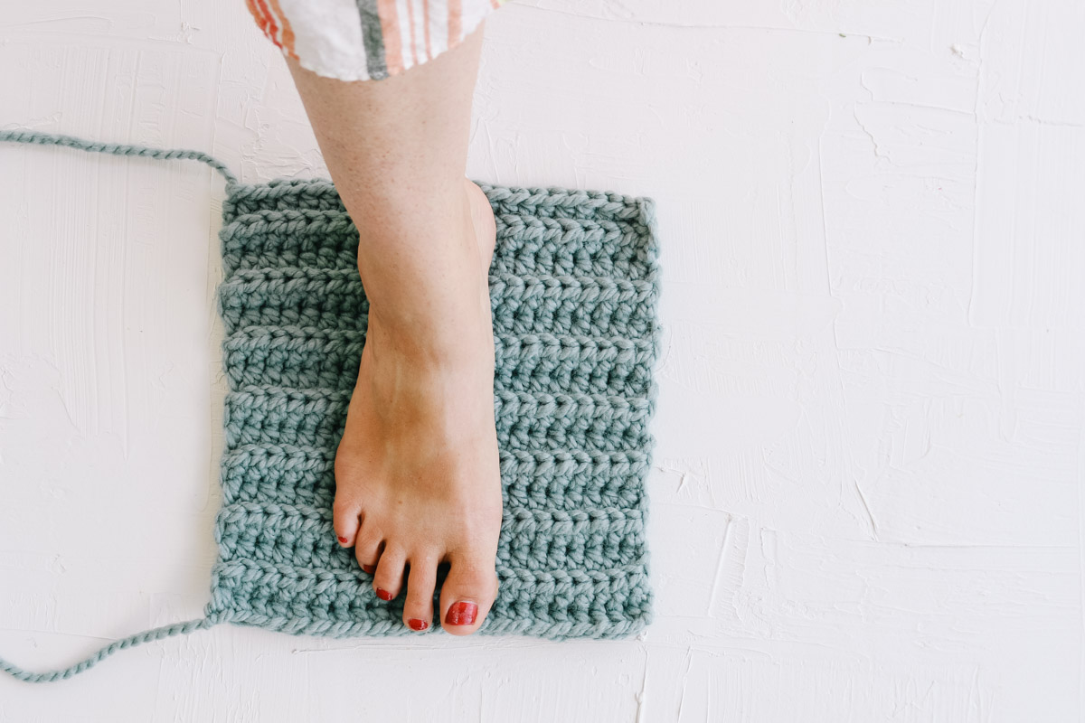 Woman's foot on a crochet rectangle as she creates simple crochet slippers.