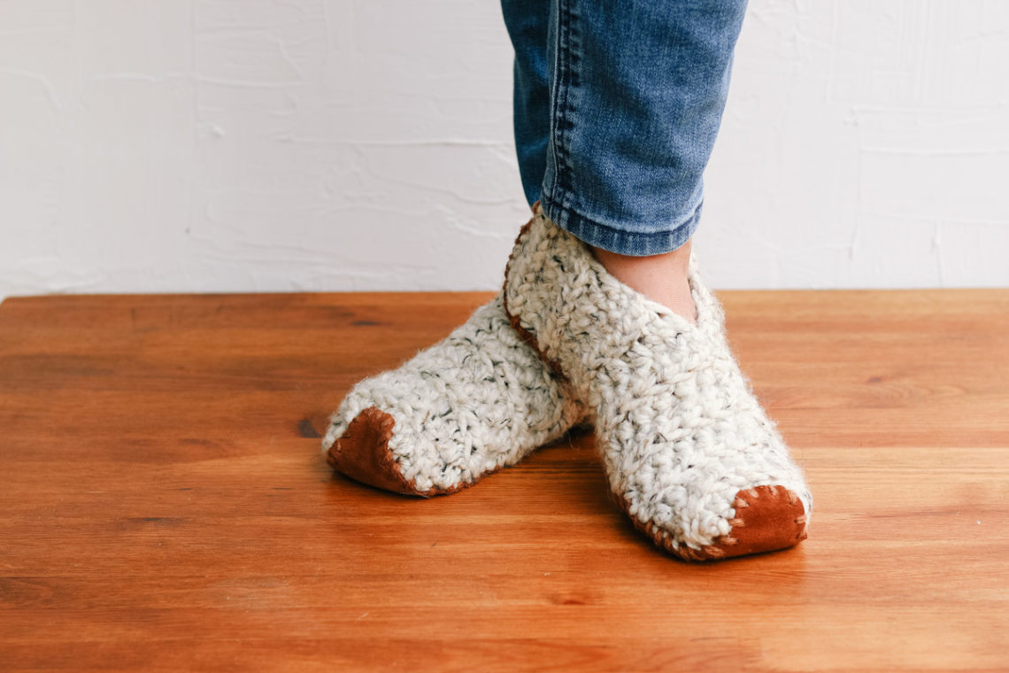 An adult woman wearing an easy pair of crochet slippers made from rectangles. Each slipper has a leather sole.