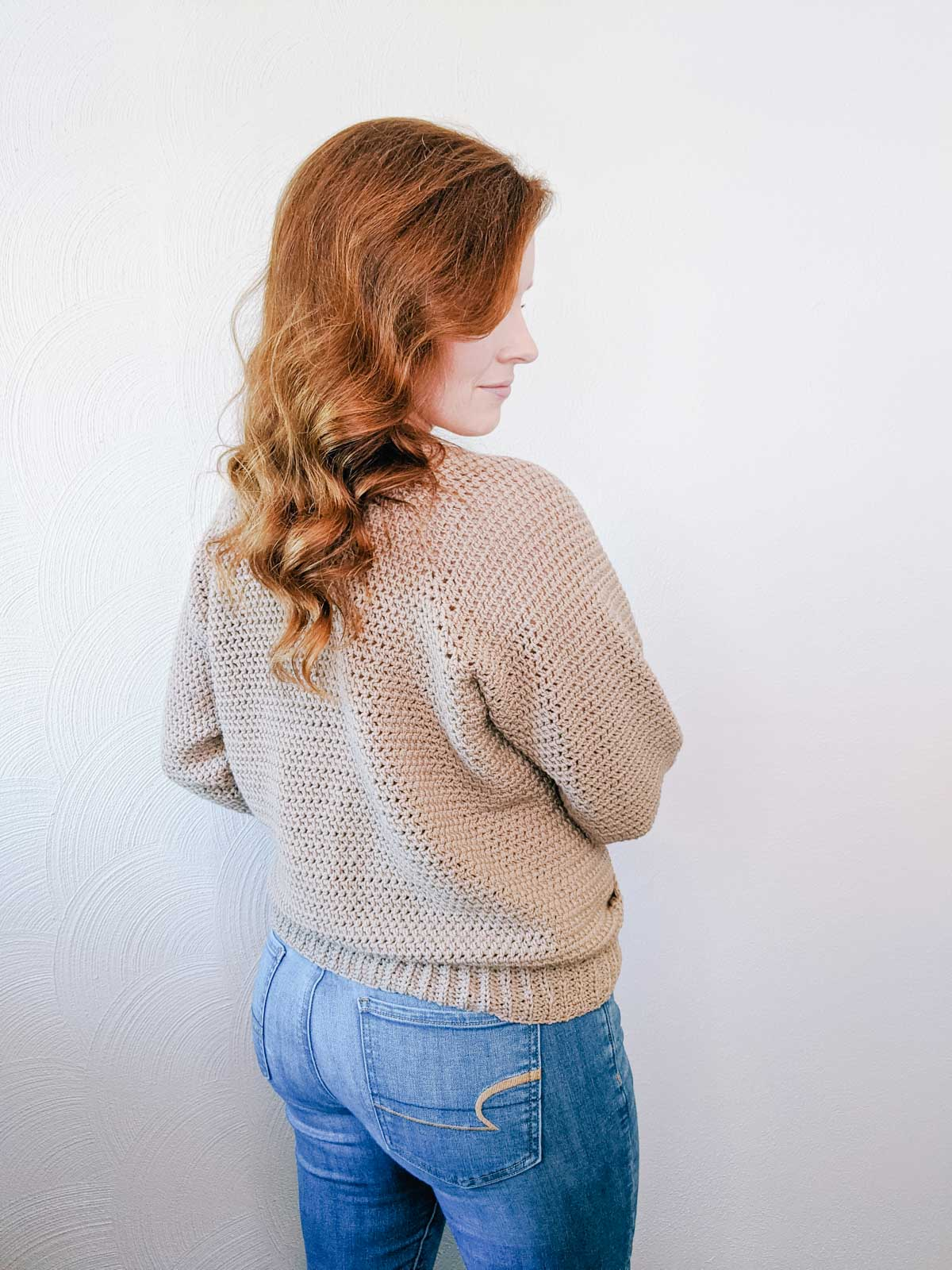 A woman standing in front of a white wall with her back to the camera. She has long red hair, and is wearing blue jeans and a crochet sweater.