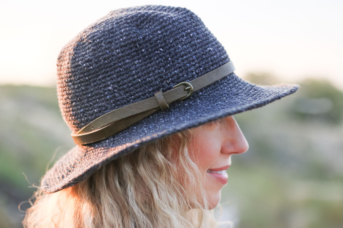 A closeup of a crochet fedora (rancher) style hat with a leather belt as a hat band. Crocheted with Lion Brand Re-Tweed yarn in the color Graphite.
