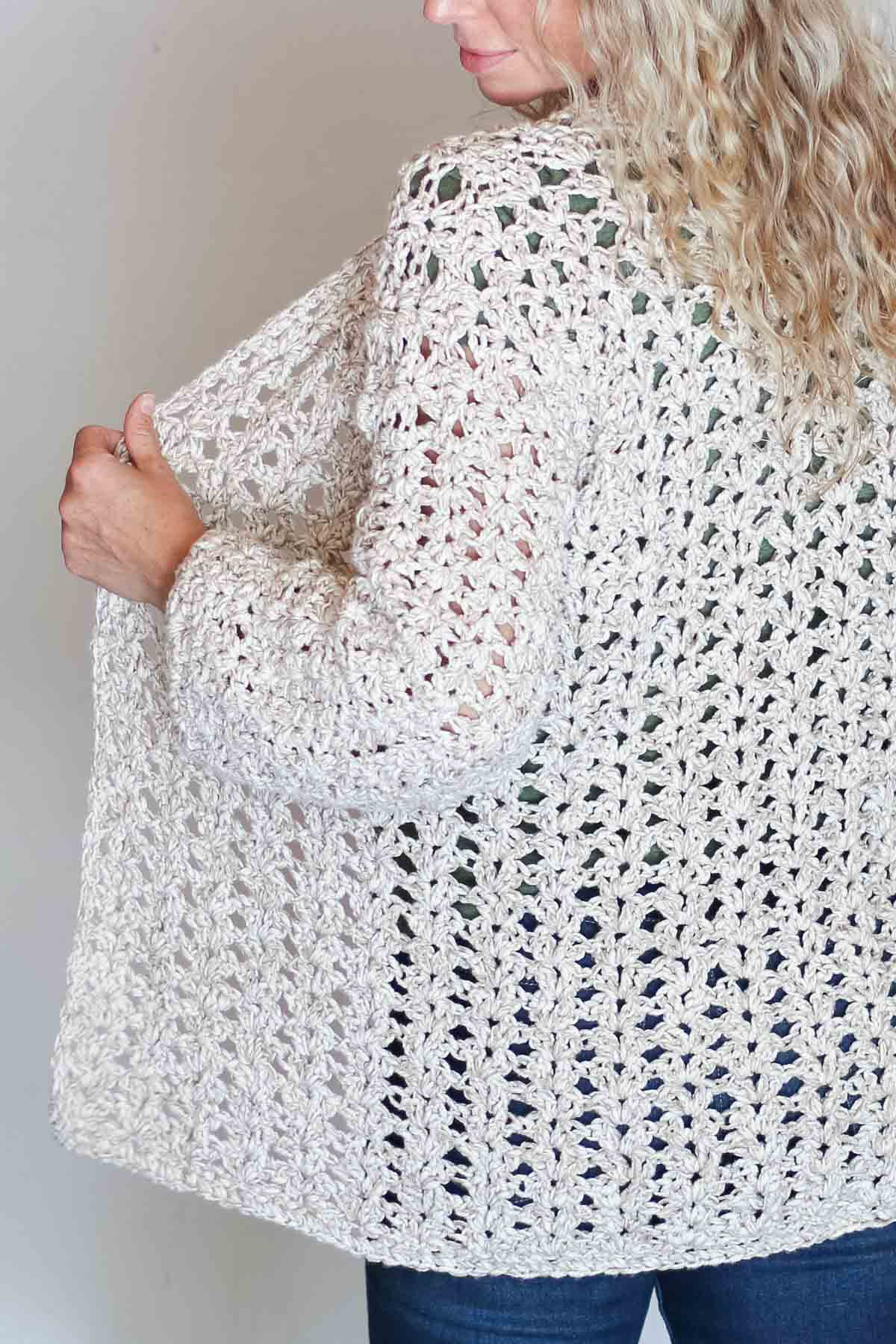 The back of a blonde woman wearing a casual crochet cardigan made with the iris stitch and Lion Brand Twisted Cotton Blend yarn.