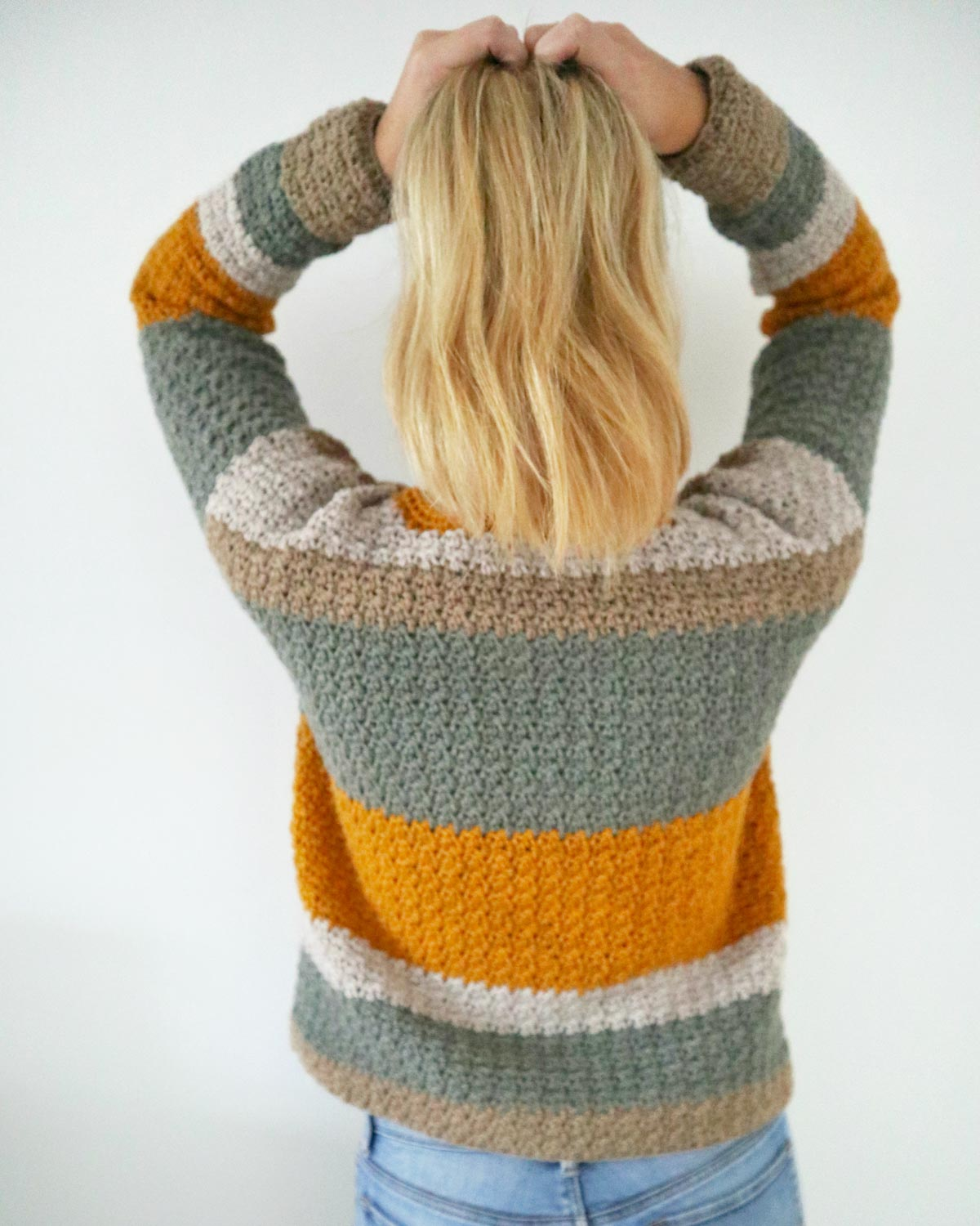 Creative construction and simple stitches come together easily in this crochet pullover pattern as viewed from behind.