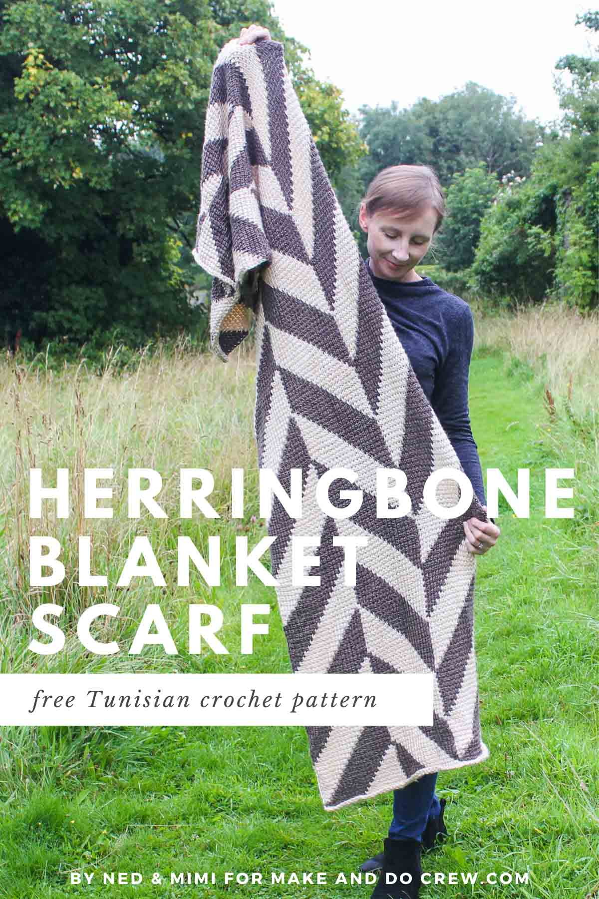 Warm and cozy! This is a picture of a woman with short, light brown hair standing in a field of green. She is displaying a Tunisian crochet blanket scarf. The scarf is made from 3 panels of Tunisian crochet to create a Herringbone pattern.