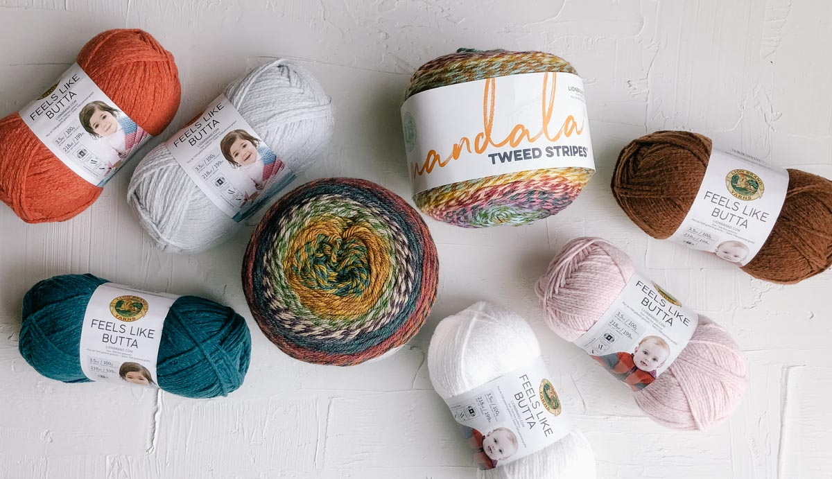 Several colors of Lion Brand Feels Like Butta yarn and Lion Brand Mandala Tweed Stripes yarn scattered on a white board.