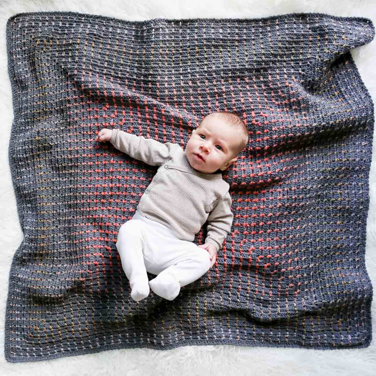 Young infant baby laying on top of a rainbow crochet blanket with modern details.