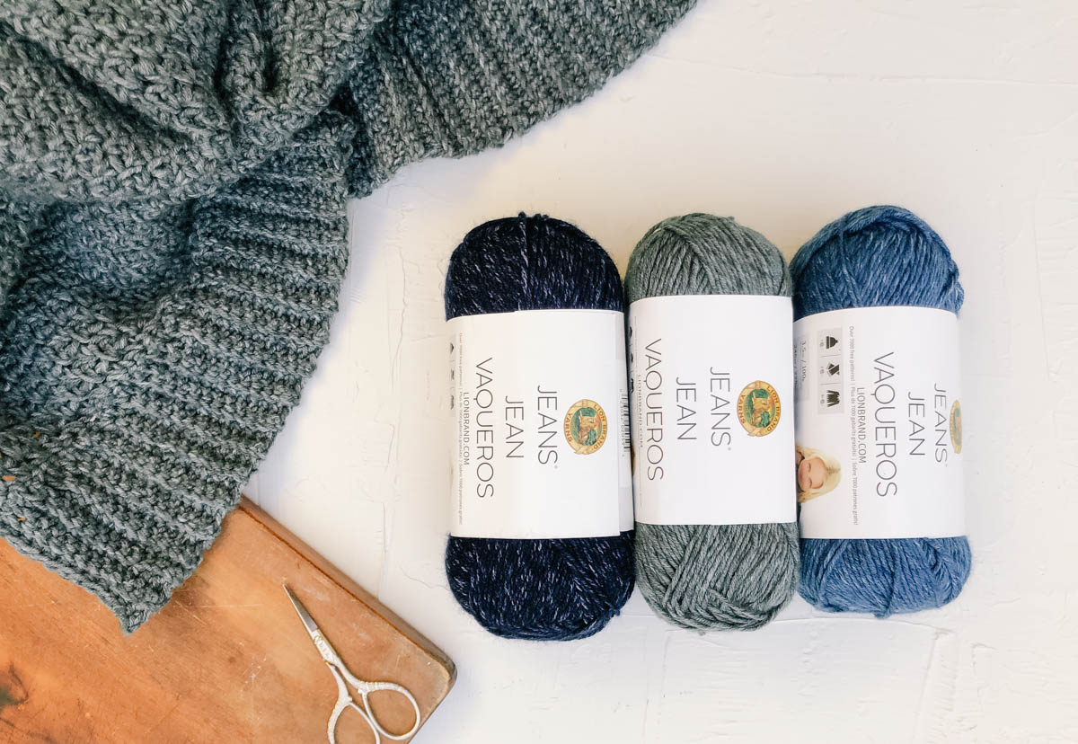Lion Brand Jeans yarn in three colors, next to a casual crochet sweater.