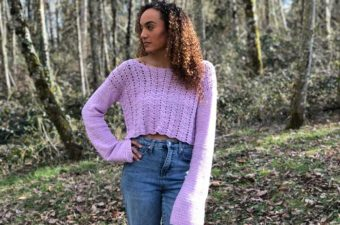 A lavender lacey crochet cropped sweater with bell sleeves.