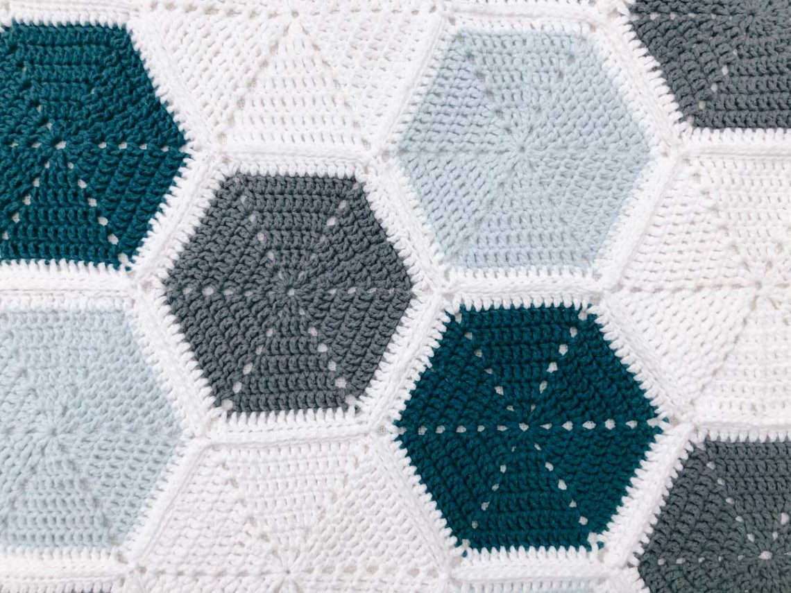 An overhead view of a crochet hexagon blanket that uses a join as you go method to piece the hexagons together.