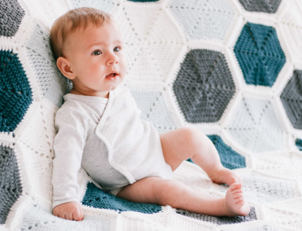 A baby laying on top of a modern crochet hexagon blanket.